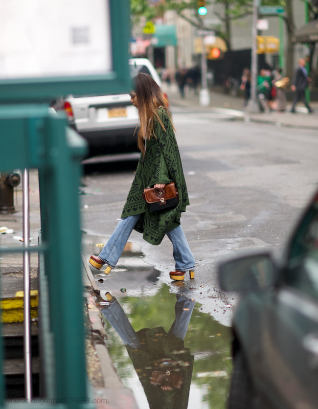woman in poncho and flared jeans