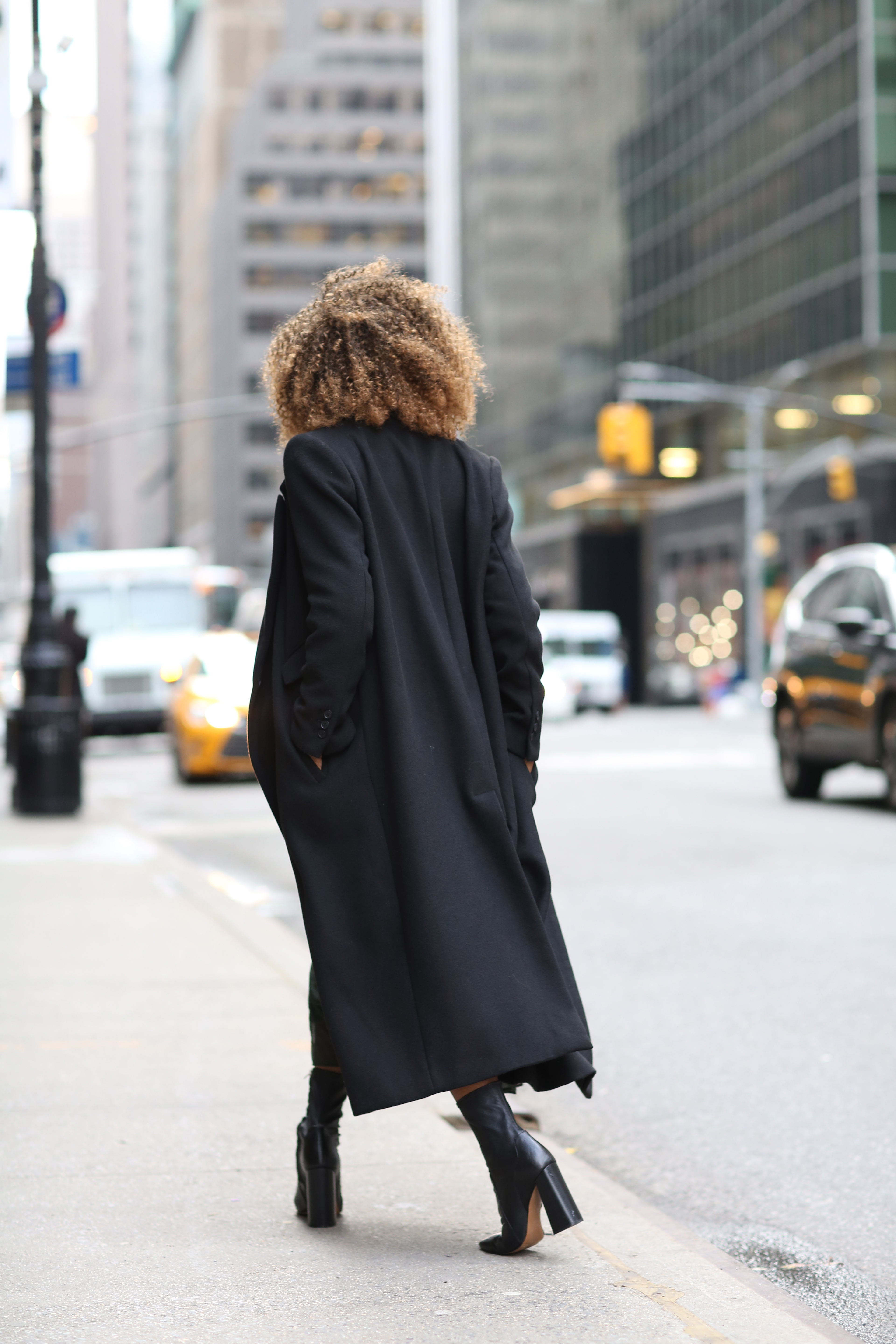 Karen Blanchard wearing a long black H&M coat with block heel ankle boots