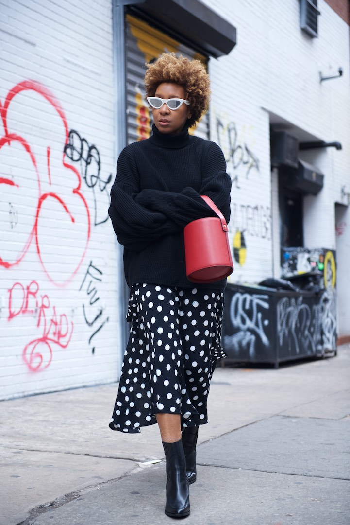 Karen Blanchard is wearing a red topshop bucket bag with a polka dot midi skirt