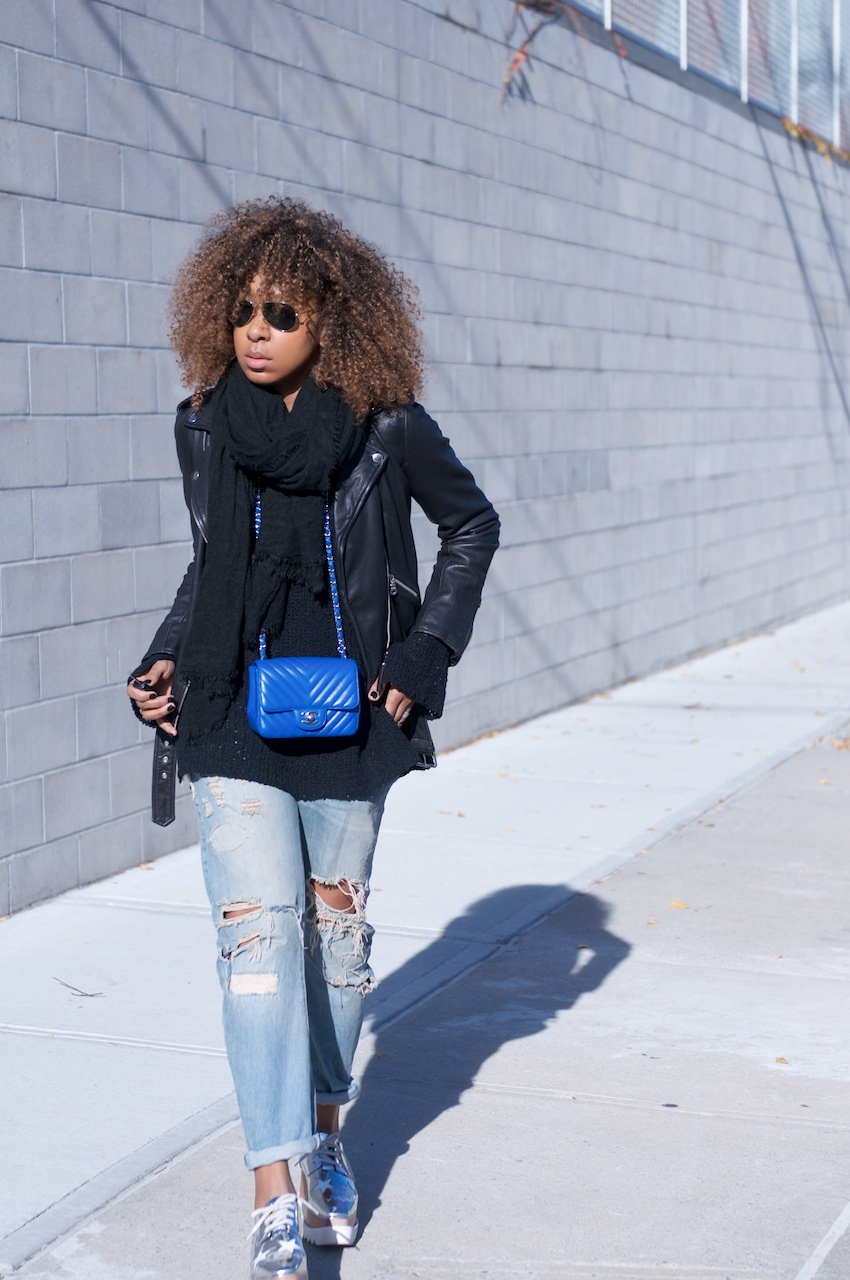 Karen Blanchard wearing a Chanel square mini bag with a Lucky Brand leather jacket and ripped denim jeans