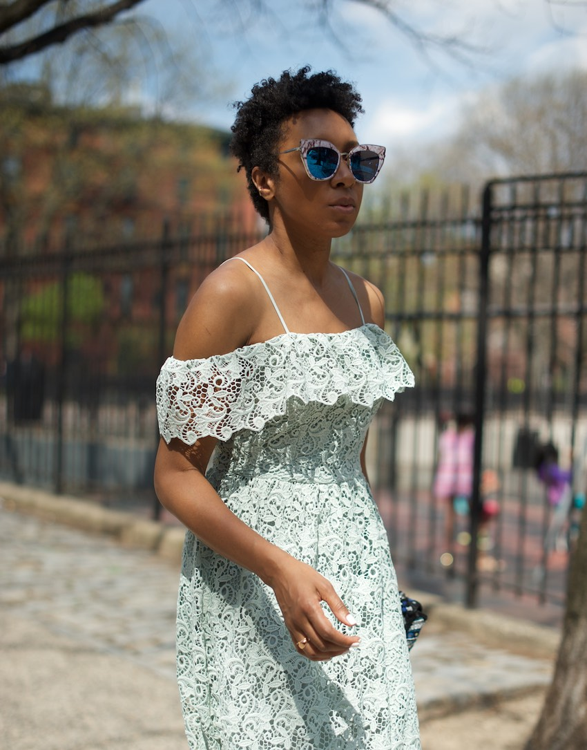 Karen blanchard with natural hair wearing statement sunglasses and an H&M lace dress