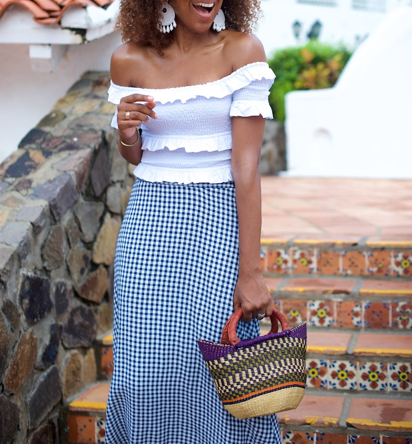 Karen Blanchard is carrying a off the shoulder white top with a gingham midi skirt and mini basket bag
